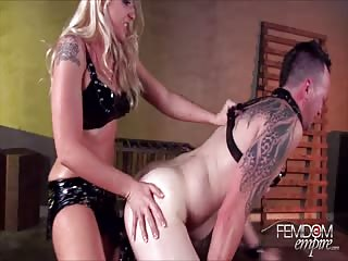 Alluring dominatrix pegging a sub tattooed man
