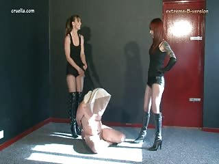 Two hardy dominatrix kick a man's balls